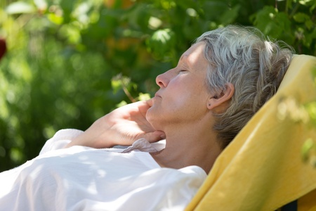 Aged woman with white hairs sleeping on lounger in her garden. photo