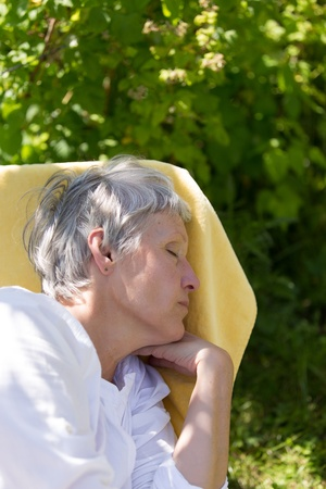 Aged woman with grey hairs sleeping on lounger in her garden. photo