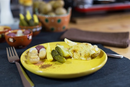 Raclette, traditional specialty of grilled yellow cheese, potatoes and pickles  photo
