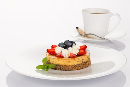 Cheesecake with strawberry, blueberry, mint and cream on white plate with cup of coffee  photo