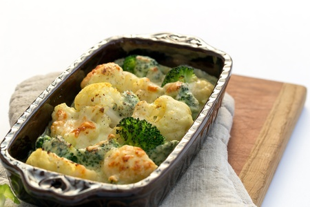 repast: Gratin of cauliflower, broccoli and cheese in brown rustic dish. Stock Photo