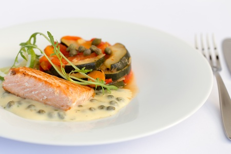 Fish fillet with lemon, vegetables and sauce in white plate. photo