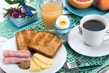 Breakfast with toast, ham, cheese, egg, grapefruit, juice and cup of coffee. photo
