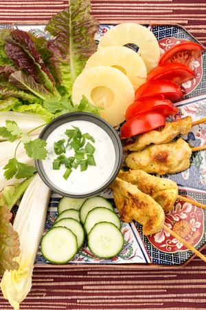 Asian food with chicken skewers, sauce, tomatoes, cucumber, pineapples, endives and salad. photo