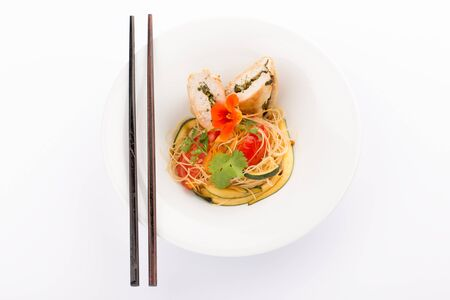 Asian food with piece of stuffed chicken, noodles, zucchini, carrots and tomatoes. photo