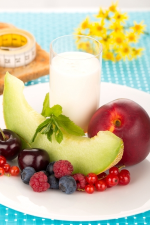repast: Healthy breakfast with a plate of fresh fruits, glass of milk.