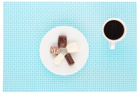 Chocolate assortment in white plate and cup of coffee. photo