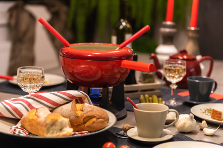 Traditional swiss cheese fondue in a red pot on concrete dining table.