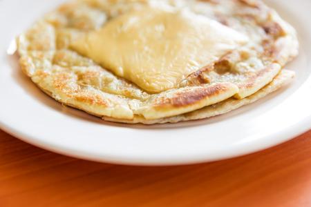 하얀 접시에 치즈와 함께 Roti