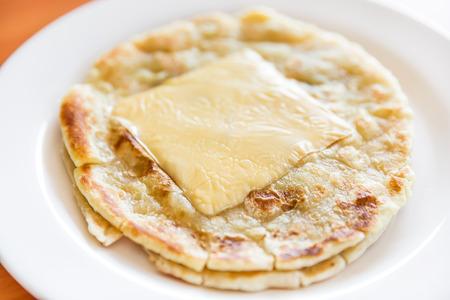 하얀 접시, roti prata에 치즈와 함께 Roti