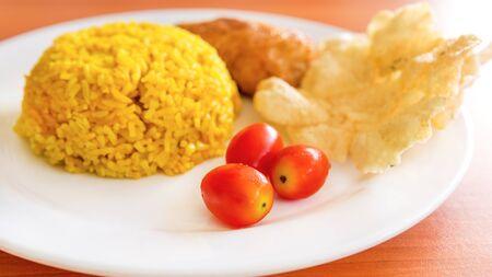indonesian food: fresh tomatoes with turmeric rice, vegetarian krupuk, Indonesian food Stock Photo