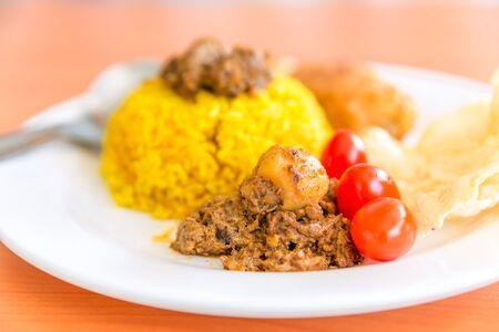 indonesian food: fresh tomatoes and vegetarian rendang with turmeric rice, Indonesian food