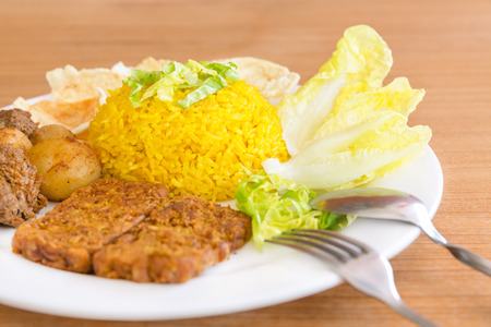 indonesian food: vegetarian rendang with turmeric rice, boiled rice, cooked with turmeric, fork and knife, Indonesian food