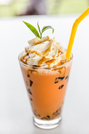 t� helado: t� con leche y helado, cristal de t� de la leche helada con crema batida