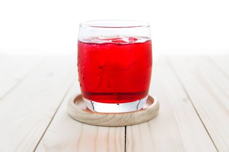 Red soda in glass on wooden table