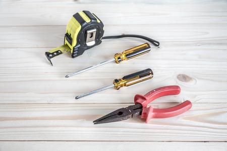 cintas metricas: alicates de punta fina, destornillador Phillips y cinta m�trica en el fondo de madera