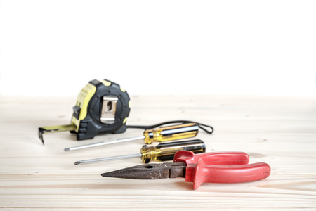screw driver: needle-nose pliers, phillips screw driver and tape measure on the wooden background Stock Photo