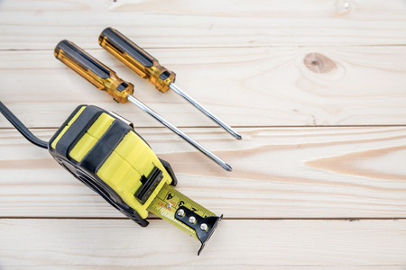 tape measure and phillips screw driver on the wooden background Stock Photo