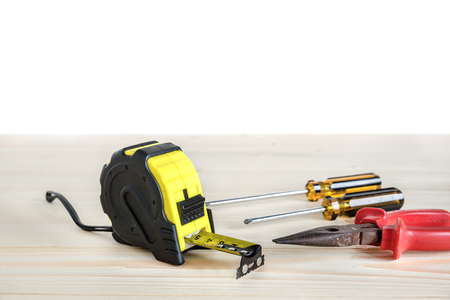 screw driver: tape measure and Phillips screw driver and needle-nose pliers on the wooden Stock Photo