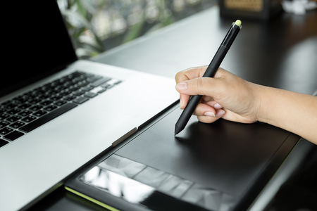 digitized: a graphic designer working with digital tablet pen, Hand of the designer with a pen on a tablet