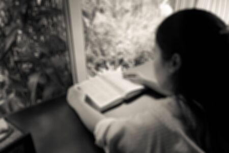 blurred image of a woman reading the holy bible in the church for religion background