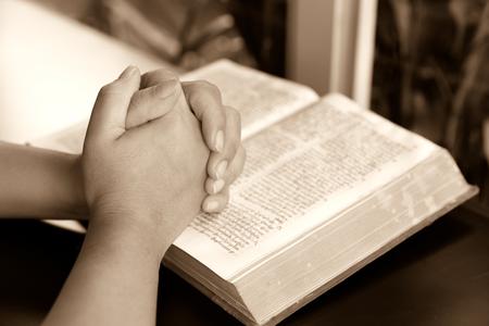 orando: orando manos y libro sobre la mesa mostrando concepto de la religión-Manos de mujer rezando con una biblia, lectura de la Biblia y orar Foto de archivo