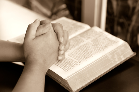 pray: praying hand and book on desk showing religion concept-Woman hands praying with a bible,Reading bible and pray Stock Photo