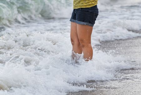 sandy feet: young girl feet on a sandy beach, woman standing on the sand beach,  just her feet and legs showing