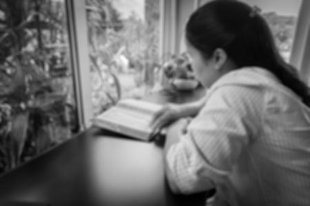 spiritual meditation creation: blurred image of a woman reading the holy bible in the church for religion background