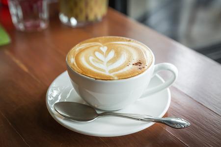 copa: taza de cappuccino, taza de café, taza de café en la mesa de madera marrón Foto de archivo
