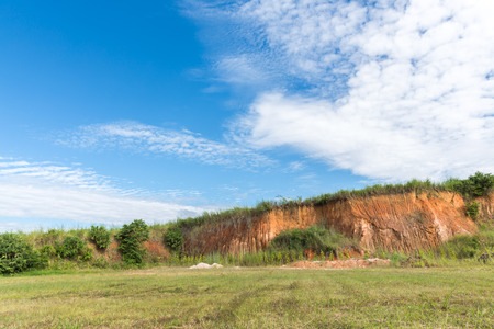 soil texture: Soil structure, Wall cliff - clay brown soil and grass, Soil cross section, green grass and blue sky