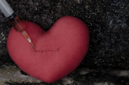 heart icon: Injection into red heart with syringe on grunge background-Sad concept Stock Photo