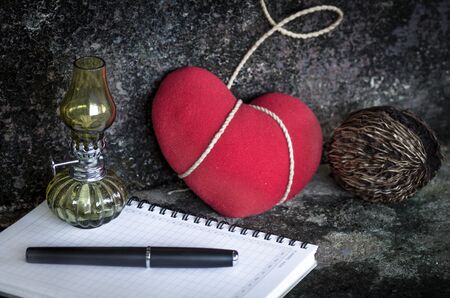 red oil lamp: Still life with old lamp and red heart-pen-notebook  in grunge background