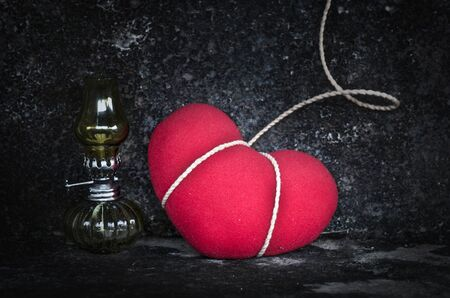 red oil lamp: Still life with red heart and old lamp in grunge background-Sad concept