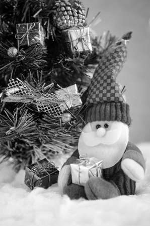 plushie: doll of santa claus and christmas tree in snow:black&white Stock Photo