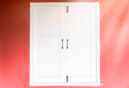 red shutters: white window on red wall background, window with white shutters on red wall