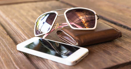 billfold: a set of smartphone and tinted sunglasses atop a brown leather wallet on wooden background - vintage effect style