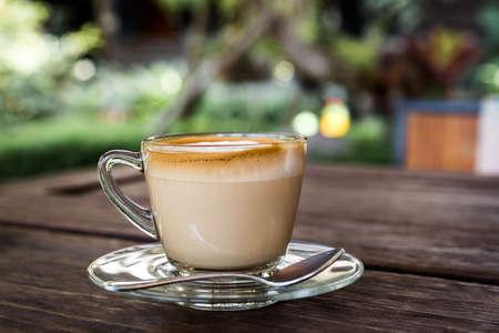 capuchino: taza de cappuccino, taza de café, taza de café en la mesa de madera marrón Foto de archivo