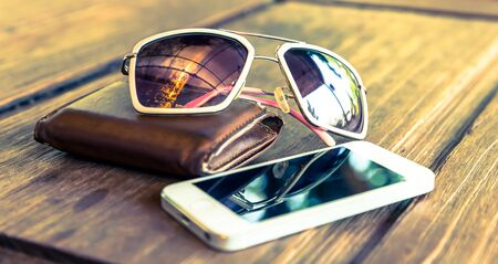 tinted: a set of smartphone and tinted sunglasses atop a brown leather wallet on wooden background - vintage effect style