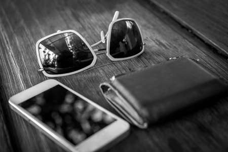billfold: a set of tinted sunglasses and smartphone, leather wallet - black and white