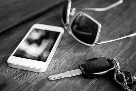 window shades: car key with smartphone and sunglasses - black and white
