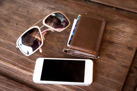 billfold: a set of tinted sunglasses and smartphone, leather wallet