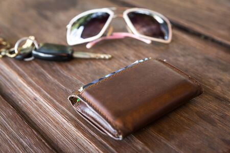 empty wallet: Brown leather wallet from the back party on wooden table, Old leather wallet on wood table