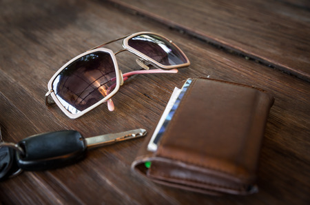 billfold: sunglasses with wallet and car remote key on wooden table