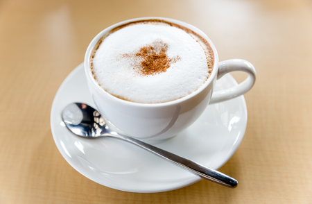 mellow: A cup of cappuccino topped with cacao powder, cup of coffee