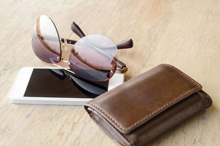 billfold: a set of tinted sunglasses and smartphone, leather wallet on wooden background-with selective focus