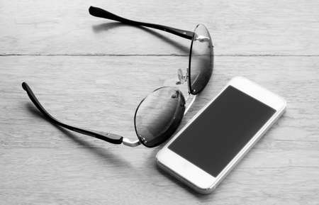 billfold: sunglasses and smartphone, leather wallet on wooden background - black and white effect style - with selective focus
