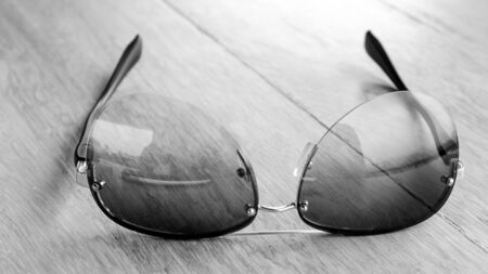 black rimmed: fashion sunglasses on wooden table-black and white effect style - with selective focus