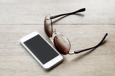 billfold: smartphone and tinted sunglasses  on wooden background - with selective focus Stock Photo