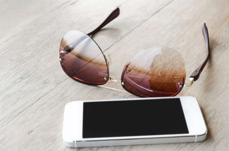 tinted: smartphone and tinted sunglasses  on wooden background - with selective focus Stock Photo